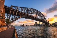 Люди идут под мост гавани с взглядом горизонта Сиднея Стоковое Фото