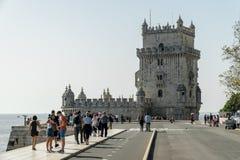 Люди идут Torre de Belem - известным ориентир ориентиром Лиссабона, Portu Стоковая Фотография