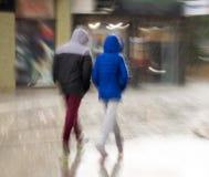 Люди идя вниз с улицы на дождливый день стоковые изображения rf