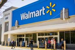 Люди идя в и приходя из магазина Walmart стоковые изображения