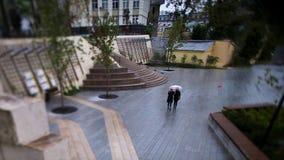 Люди идя в парк в течение дня footage Люди под зонтиком идут в парк Стоковое Изображение