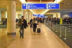 Люди идя в регистрацию и снабжая зону билетами на международном аэропорте 1 Орландо стоковое фото