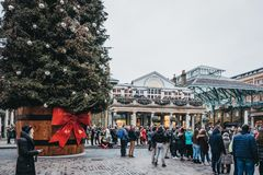 Люди идя гигантской рождественской елкой в рынке Ковент Гардена, Лондоне, Великобритании стоковое изображение rf