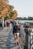 Люди идя на пешеходную дорожку наряду с рекой Влтавы в Праге взгляд городка республики cesky чехословакского krumlov средневековы стоковое фото rf