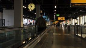 Люди идя на плоский лифт в авиапорте, спешности выстрогать, проходя стержнями сток-видео