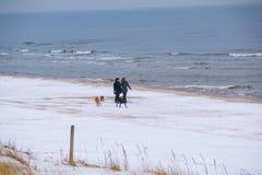 Люди идя на пляж покрытый с снегом стоковые фото