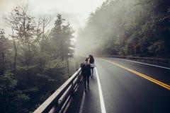 Люди идя на сторону дороги в лесе гор Стоковые Изображения