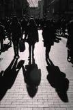 Люди идя на улицу Городская толпа внутри освещает контржурным светом стоковое изображение