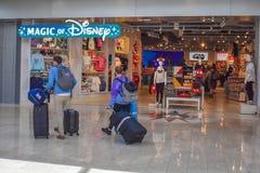 Люди идя с багажем близко к магазину Дисней на международном аэропорте 1 Орландо стоковые изображения