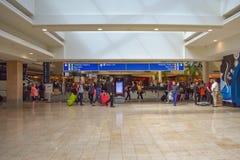 Люди идя с багажем к различным терминалам и взгляду сверху знака снабжать билетами и регистрации голубого на Орландо международно стоковая фотография rf