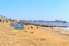 Люди имея потеху на пляже Southwold с пристанью Southwold стоковые изображения