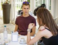 Люди и женщины сидя на выпивать таблицы Стоковые Изображения RF