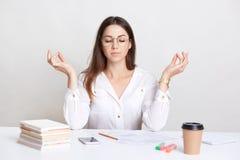 Люди и концепция духовности Ослабленная молодая женщина брюнета представляет на рабочем месте в знаке mudra, наслаждается мирной  стоковое фото rf