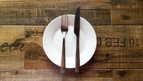 Люди и нож на белом блюде стоковое изображение