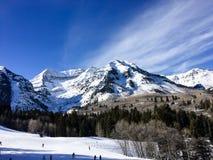 Люди катаясь на лыжах вниз с горы Стоковые Изображения
