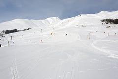 Люди катаясь на лыжах в piste лыжи снега в горных вершинах Швейцарии на зимние отдыхи Стоковое Фото