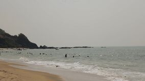 Люди купая в океанских волнах около желтого песчаного пляжа акции видеоматериалы