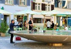 Люди купая собак в фонтане на квадрате Munsterhof в Цюрихе Стоковое Фото