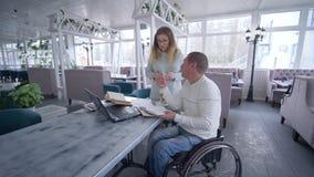 Люди менеджеров ресторана с ограниченными возможностями на кресло-коляске обсуждают запланировать и начать идеи дела с женщиной п видеоматериал