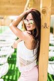 Люди, мода, лето и концепция пляжа - счастливая молодая женщина в одеждах лета над бассейном на пляжном комплексе Стоковые Изображения RF