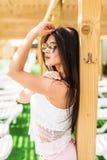 Люди, мода, лето и концепция пляжа - счастливая молодая женщина в одеждах лета над бассейном на пляжном комплексе Стоковая Фотография