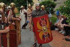 Люди наблюдают как актеры в римских солдатах в прошлом прогулки костюма стоковые фото