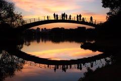 Люди наблюдают красочный заход солнца озером, парком Ibirapuera, Сан-Паулу, Бразилией Стоковая Фотография RF