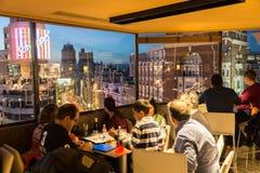 Люди наслаждаясь вечерними напитками и изумляя панорамные виды Мадрида на сумраке на баре крыши El Corte Ingles стоковое фото
