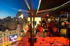Люди наслаждаясь вечерними напитками и изумляя панорамные виды Мадрида на сумраке на баре крыши El Corte Ingles стоковые фотографии rf