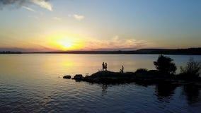 Люди наслаждаясь заходом солнца берега реки сток-видео