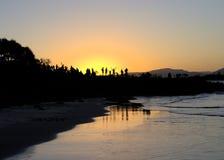 Люди наслаждаясь заходом солнца на австралийском пляже Стоковое Изображение