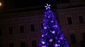 Люди наслаждаясь праздненствами рождества приближают к красивому дереву Нового Года в большом городе акции видеоматериалы