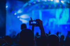 Люди наслаждаясь рок-концертом и принимая фото с сотовым телефоном на музыкальный фестиваль стоковые фото