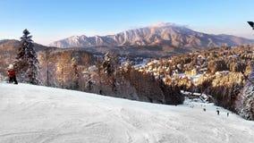 Люди наслаждаясь солнечным днем на лыжном курорте
