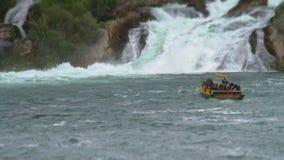 Люди на заплыве шлюпки к могущественному Rhine Falls, и рыболовы улавливают рыб видеоматериал
