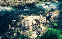 Люди на камнях кучи озера стоковое изображение
