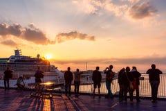 Люди на палубе восхищают заход солнца Стоковое Изображение RF
