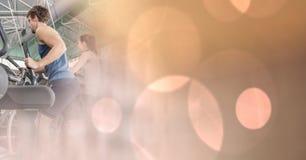 Люди на перекрестных тренерах с bokeh персика переводят Стоковая Фотография RF