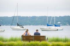 Люди на скамейке в парке с яхтами и водой в предпосылке Стоковые Изображения