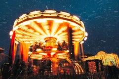 Люди на carousel около красной площади украшенной и аранжированной на Новый Год рождества Рождество справедливое Светящая карусел стоковые изображения rf