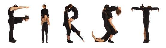 Люди одетьнные чернотой формируя ПЕРВОЕ слово стоковые фотографии rf