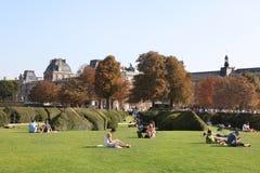 Люди ослабляют на парке Tuileries лужайки перед жалюзи Стоковые Изображения RF