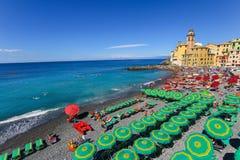 Люди ослабляя на пляже и базилике Santa Maria Assunta на заднем плане, Camogli Стоковые Фото