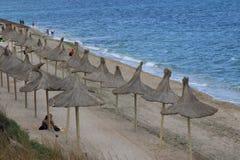 Люди ослабляя на пляже на пасмурной погоде Стоковая Фотография