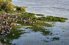 Люди отдыхая на затопленном берег реки береге реки, Реке Висла, Польше стоковая фотография