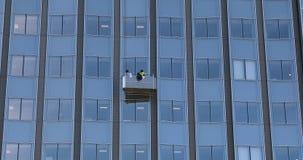 Люди очищая стеклянное Windows на высоком здании подъема видеоматериал