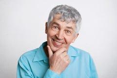 Люди, пенсия и положительная концепция эмоций Довольный зрелый мужчина с серыми волосами, держит руку под подбородком, носит офиц стоковое изображение rf