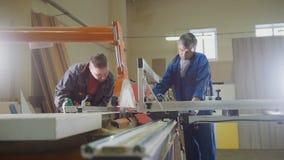 Люди - плотники режут древесину на электрической пиле на фабрике мебели стоковые изображения rf