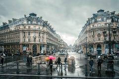 Люди под покрашенными зонтиками бегут в дожде на улицах Парижа, Франции Стоковое фото RF