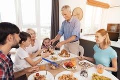 Люди положили испеченного индюка к их родственникам, которые собрали на праздничной таблице на благодарение Стоковая Фотография RF